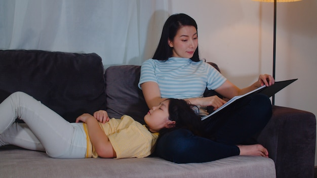 Young asian mother read fairy tales to her daughter at home. happy chinese family relax with teen girl who sleep while listening to tales lying on bed in bedroom at modern house at night .