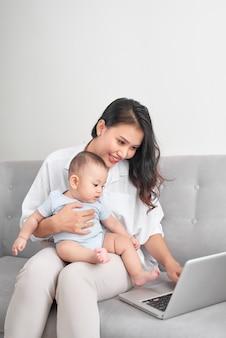 Молодая азиатская мать сидит на диване у себя дома с компьютером и ее дочерью