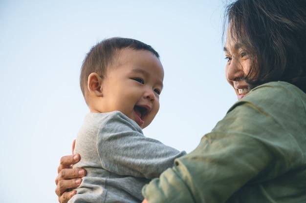 彼女の息子または自宅の公園でかわいい赤ちゃんと一緒に若いアジアの母親。