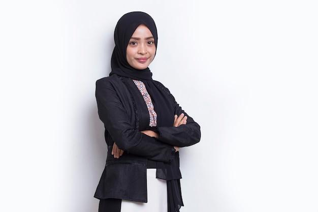 白い背景に腕を組んでヘッドスカーフ笑顔の若いアジアのイスラム教徒のビジネス女性