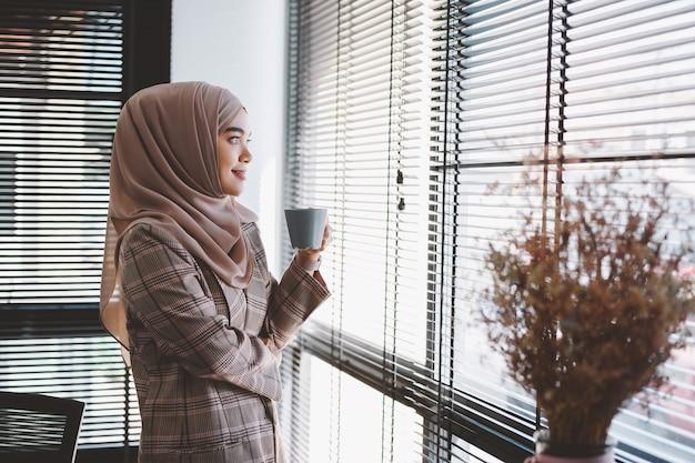 ガラスの壁の横に立っているスマートカジュアルウェアの若いアジアのイスラム教徒のビジネス女性