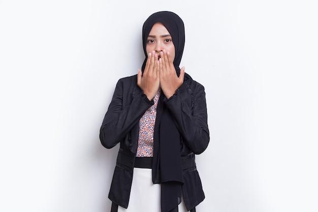 젊은 아시아 이슬람 비즈니스 여성은 실수로 손으로 입을 가리고 충격을 받았습니다.