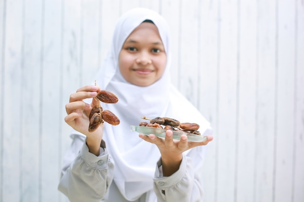 Young asian muslim female smiling and offering dates on her hand while holding dates on the plate