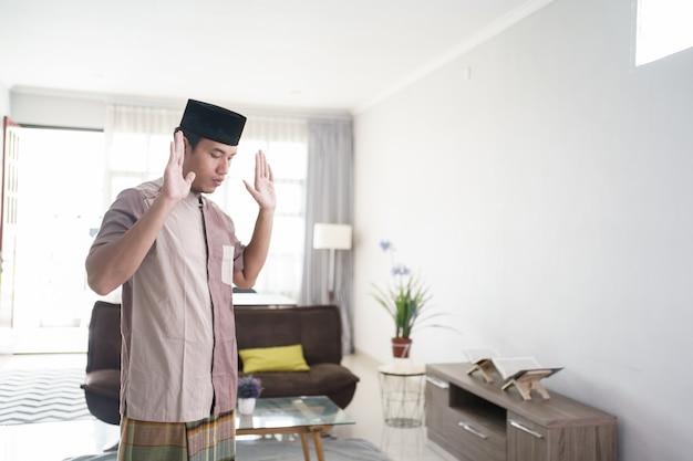 Молодой азиатский мусульманин молится дома такбир перед началом молитвы