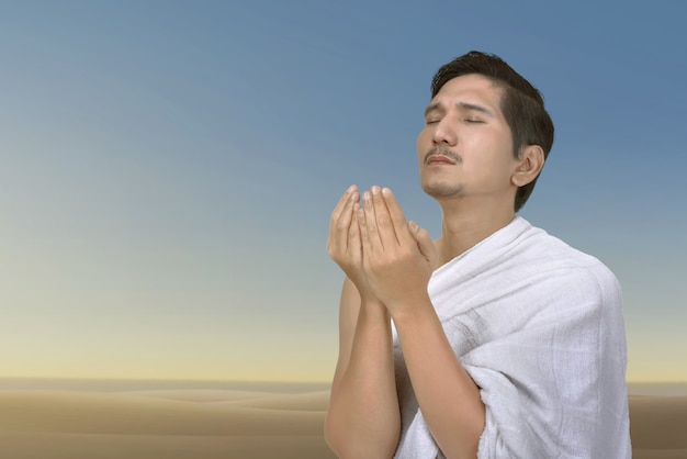 Young asian muslim man praying to god