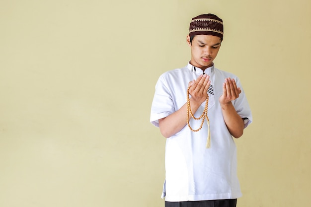 Young asian muslim man praying while holding rosary beads with copy space