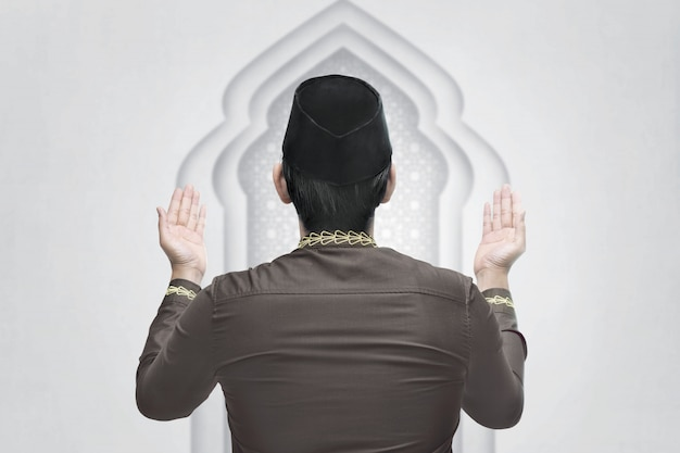 Young asian muslim man raising hand and pray