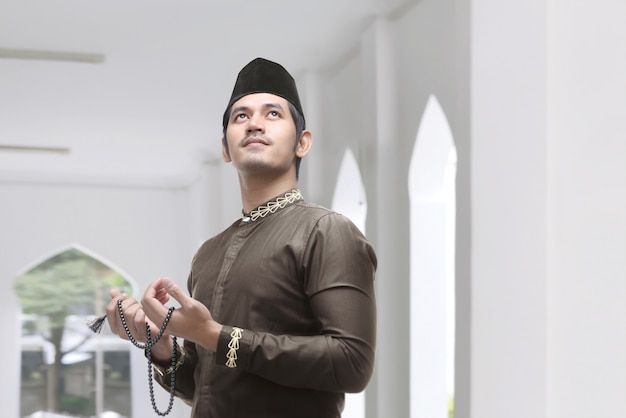 Young asian muslim man with prayer beads praying