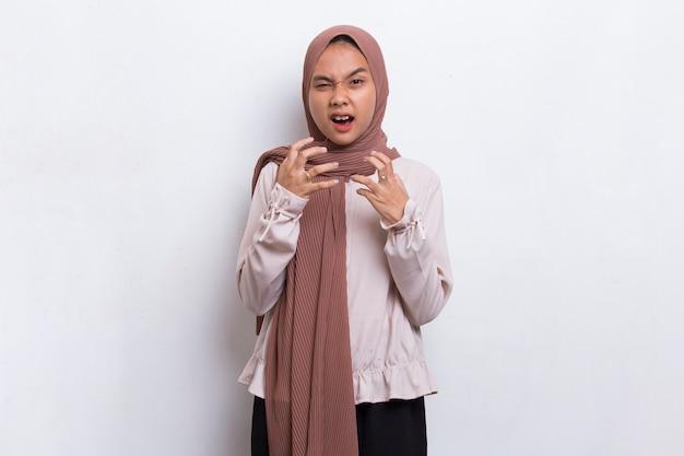 若いアジアのイスラム教徒の女性怒っている感情的な叫び声と白い背景で叫ぶ