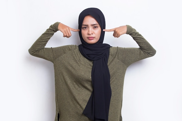 Young asian muslim woman covering both ears with hands isolated on white background