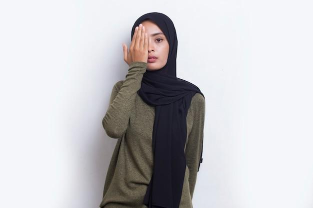 Молодая азиатская мусульманская женщина закрывает один глаз рукой, изолированной на белом фоне
