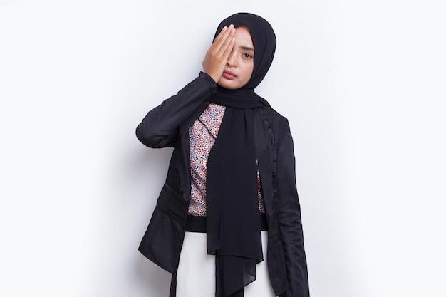 흰색 배경에 격리된 손으로 한쪽 눈을 덮고 있는 젊은 아시아 이슬람 여성