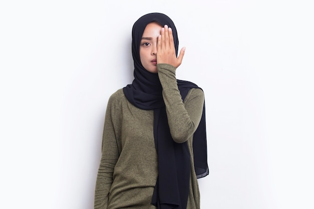 Young asian muslim woman covering one eye with hand isolated on white background