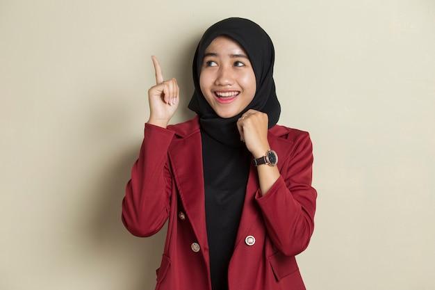 젊은 아시아 무슬림 여성은 좋은 생각이 있습니다. 회색 배경에 고립 행복 웃는 소녀.
