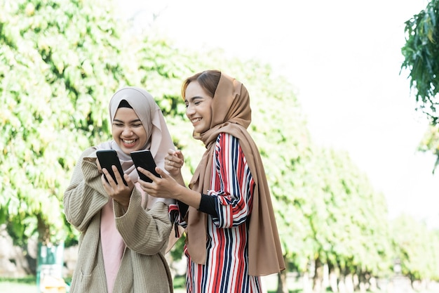 Young asian muslim woman in head scarf meet friends and using phone in the park