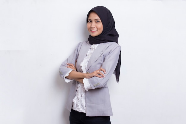 Young asian muslim woman in head scarf smile with arms crossed on white background