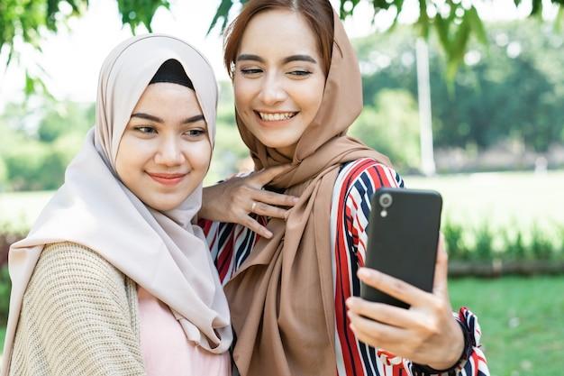 ヘッドスカーフの若いアジアのイスラム教徒の女性は友達に会い、公園で自分撮りやビデオ通話のために電話を使用しています