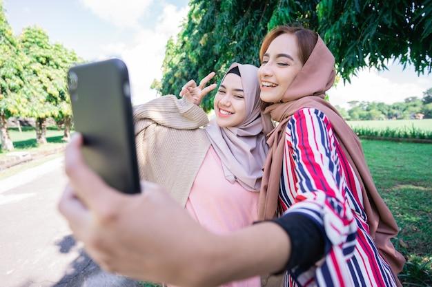 ヘッドスカーフの若いアジアのイスラム教徒の女性は友人に会い、セルフィーやビデオ通話のために公園で電話を使用しています