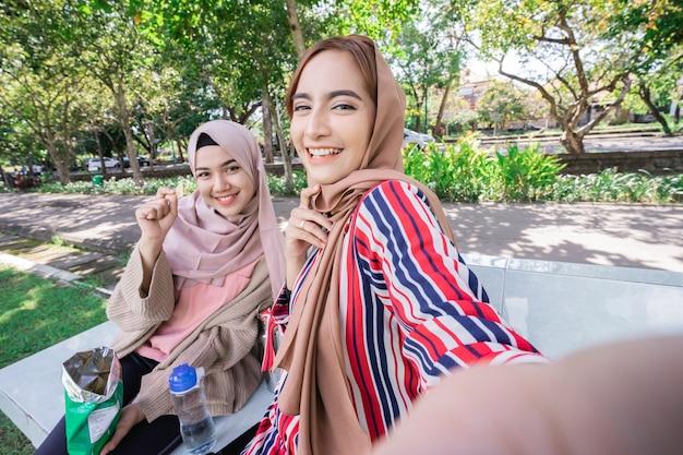 ヘッドスカーフの若いアジアのイスラム教徒の女性は友達に会い、公園で電話を使って一緒に自分撮りをします