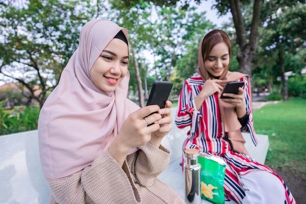 ヘッドスカーフの若いアジアのイスラム教徒の女性は、いくつかの軽食を楽しみながら公園で友人に会い、電話を使用しています