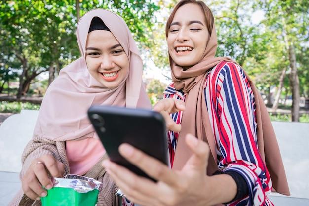 ヘッドスカーフの若いアジアのイスラム教徒の女性は、友人に会い、公園で電話を使用しています