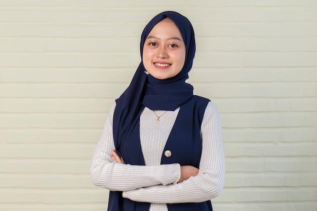 腕を組んでヘッドスカーフ笑顔の若いアジアのイスラム教徒の女性