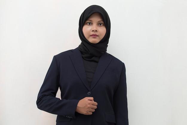 Молодая азиатская мусульманская женщина в головном платке улыбается со скрещенными руками