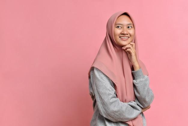 コピースペースを見たり、アイデアを考えている若いアジアのイスラム教徒の女性。ピンクの背景で隔離