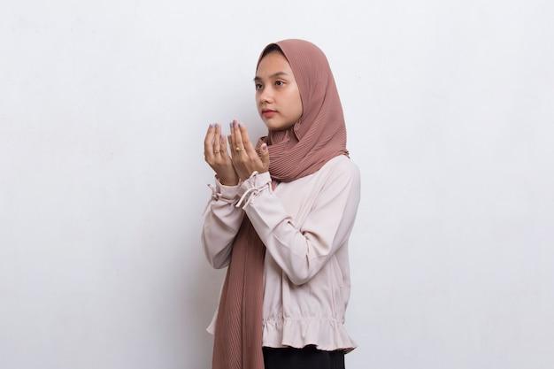 흰색 배경에 고립 된 기도 젊은 아시아 이슬람 여자