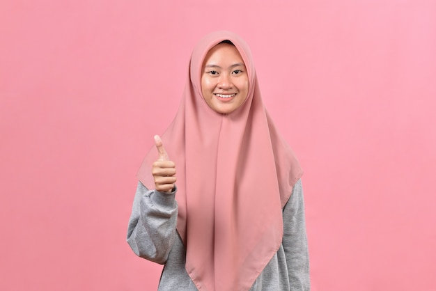 ピンク色の背景に親指を示す若いアジアのイスラム教徒の女性。コピースペースをモックアップします。親指を立てる。