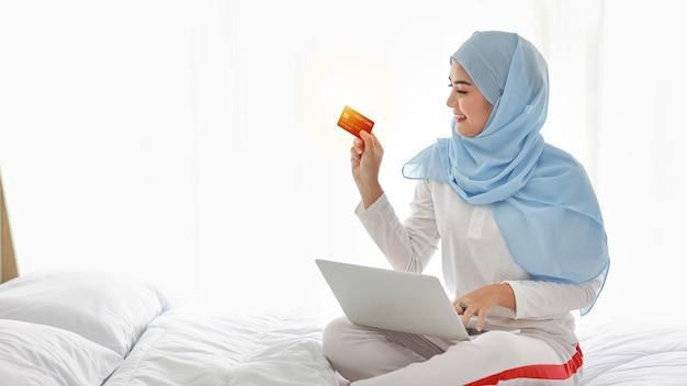 ベッドに座って、寝室でコンピューターとクレジットカードを保持している若いアジアのイスラム教徒の女性。ヒジャーブの購入またはオンライン支払いでパジャマの美しい少女。ライフスタイルとテクノロジーのコンセプト