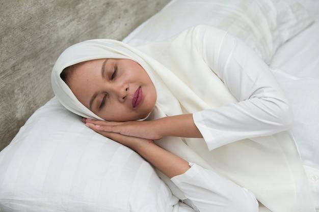 피곤한 꿈을 자고 젊은 아시아 무슬림 여성. 잠자는 척하고 몸짓을하는 여성. 지쳐 잠들 졸린 피곤한 여자.