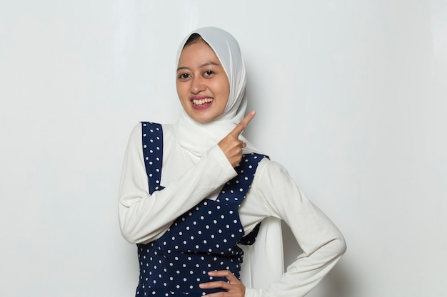 Young asian muslim woman  smiling confident pointing with fingers to different directions