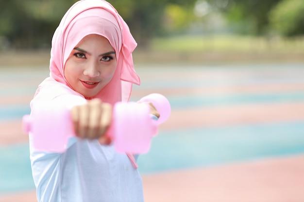 緑の木の背景と運動のために屋外でダンベルを立って持ち上げる若いアジアのイスラム教徒の女性