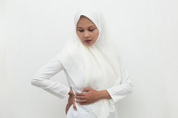 Young asian muslim woman suffering low back pain and waist lumbar pain