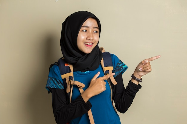Young asian muslim woman traveler wearing hijab smiling confident pointing with fingers to different directions.