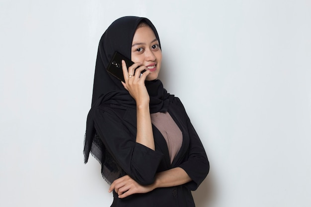 Young asian muslim woman using mobile phone on white background