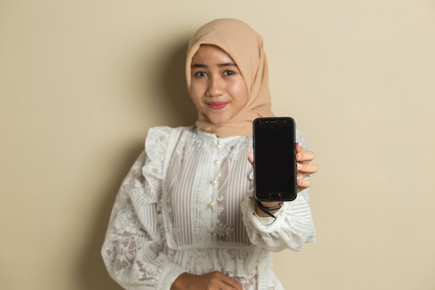 Young asian muslim woman wearing hijab showing blank screen mobile phone