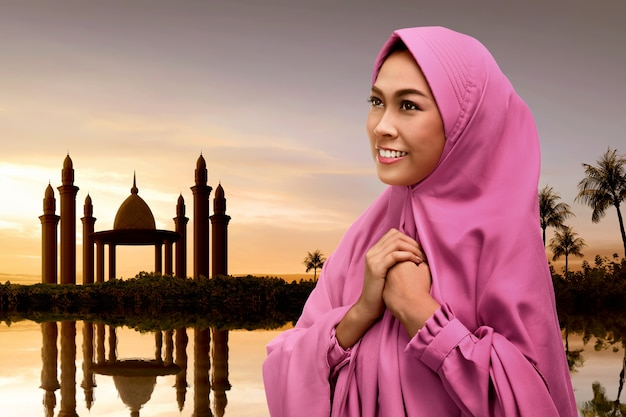 Young asian muslim woman with veil praying to god