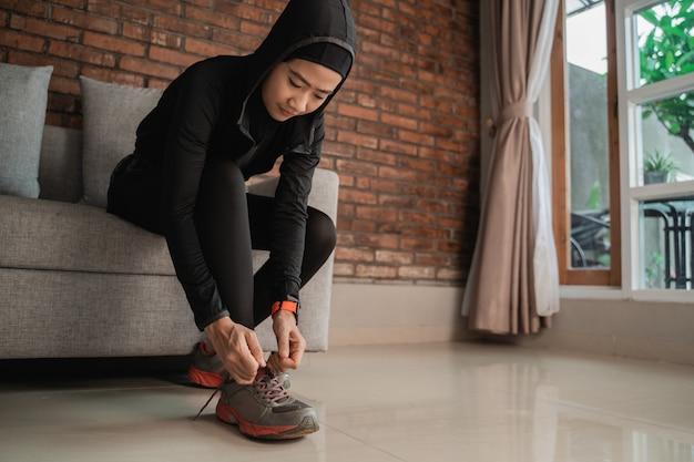 若いアジアのイスラム教徒の女性はスポーツヒジャーブを着用し、ドアで靴ひもを修正