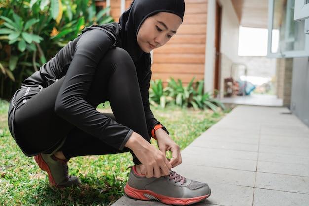 若いアジアのイスラム教徒の女性はジョギングの前にスポーツヒジャーブを着用し、靴ひもを修正します