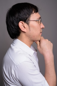 Young asian nerd man wearing eyeglasses against gray wall