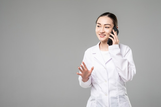 Young asian nurse with a stethoscope talking on the phone, isolated over white wall.