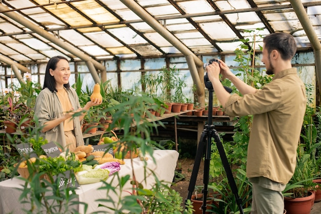 Young asian nutritionist holding pumpkin and making video about food in greenhouse