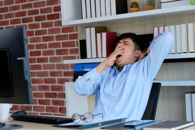 Young asian office man yawning while working on paperwork and computer