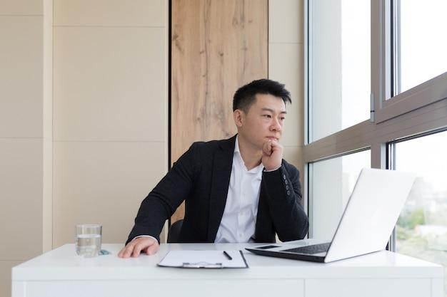 사무실에서 두통으로 고통받는 젊은 아시아 회사원은 약을 물과 함께 마신다. 심한 통증으로 실내 컴퓨터에서 양복을 입은 아픈 남자가 직장에서 약물을 사용합니다