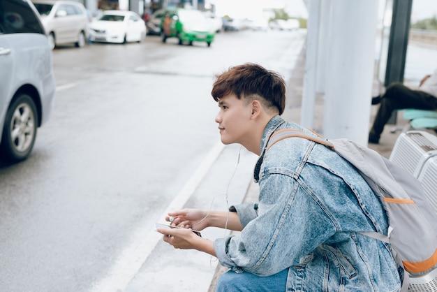 공항에서 전화로 택시를 기다리는 젊은 아시아 승객