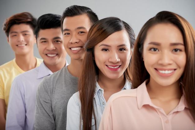 Giovani asiatici di fronte alla fotocamera in piedi uno per uno in fila sorridendo