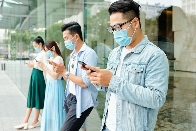 Young asian people wearing medical masks due to coronavirus pandemic, they are standing outside the shopping mall and texting friends or using social media