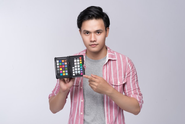 스튜디오에서 일하는 동안 컬러 체커 카드를 들고 있는 젊은 아시아 사진작가